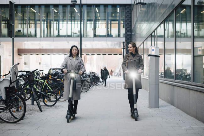 Pleine longueur de collègues féminines confiantes chevauchant scooter électrique sur le sentier en construisant en ville — Photo de stock
