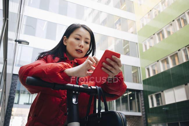 Commuter fêmea que usa o telefone esperto ao inclinar-se no guiador elétrico do scooter do impulso na cidade — Fotografia de Stock