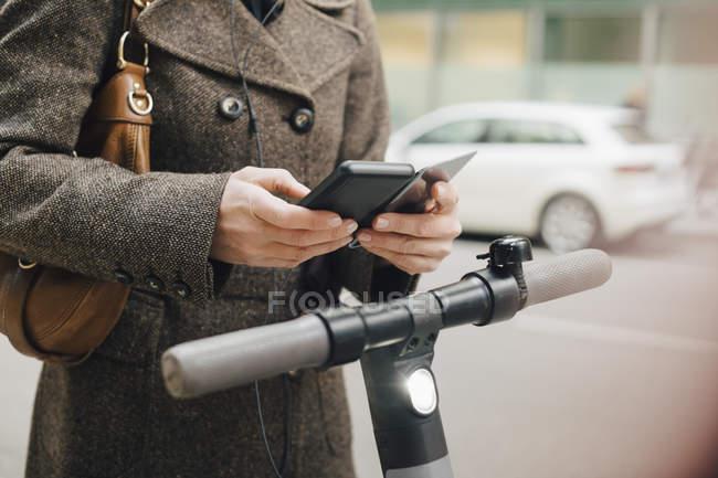 Pendlerinnen nutzen Smartphone im Stehen mit Elektroauto in der Stadt — Stockfoto