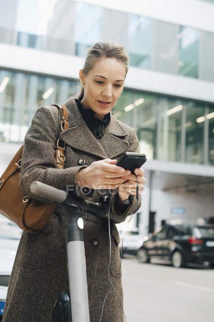Selbstbewusste Geschäftsfrau mit Smartphone im Stehen mit Elektroroller in der Stadt — Stockfoto