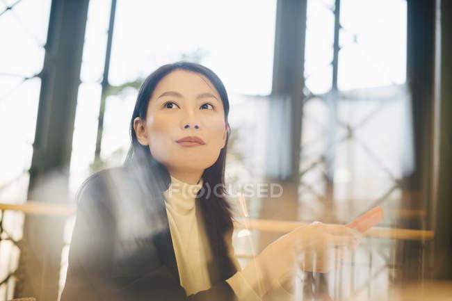 Fiduciosa donna d'affari in possesso di smart phone mentre distoglie lo sguardo in mensa ufficio — Foto stock