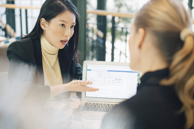 Confident businesswoman discussing over laptop with female colleague at office — Stock Photo