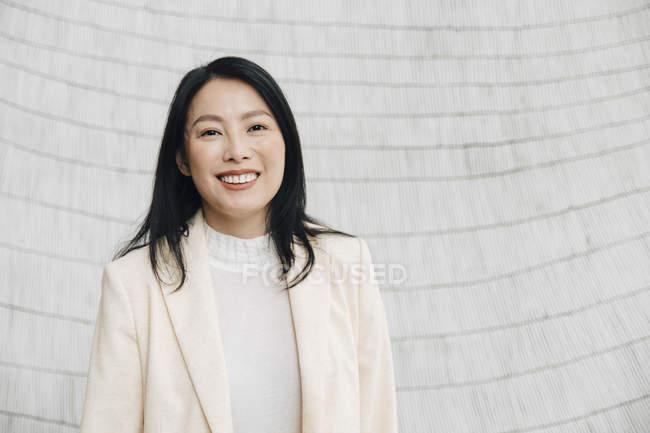 Ritratto di donna d'affari sorridente in giacca in piedi contro il muro in ufficio — Foto stock