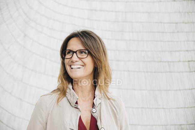Улыбающаяся деловая женщина смотрит в сторону, стоя у стены офиса — стоковое фото