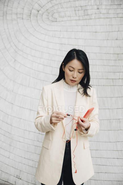 Donna d'affari fiduciosa che tiene smartphone e auricolari contro il muro in ufficio — Foto stock