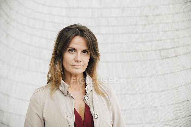Portrait of confident businesswoman standing against wall at office — Stock Photo