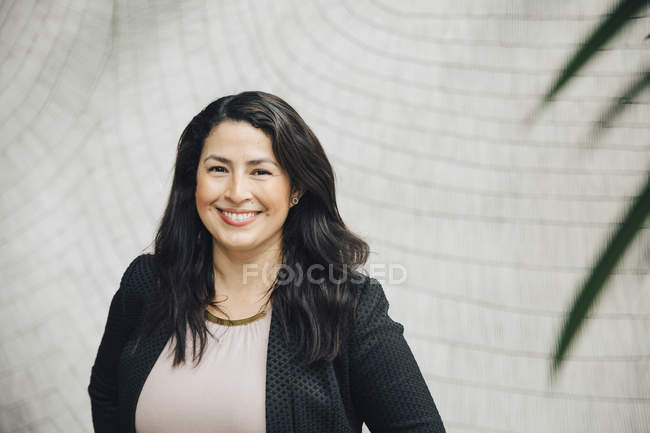 Портрет улыбающейся деловой женщины, стоящей у стены офиса — стоковое фото