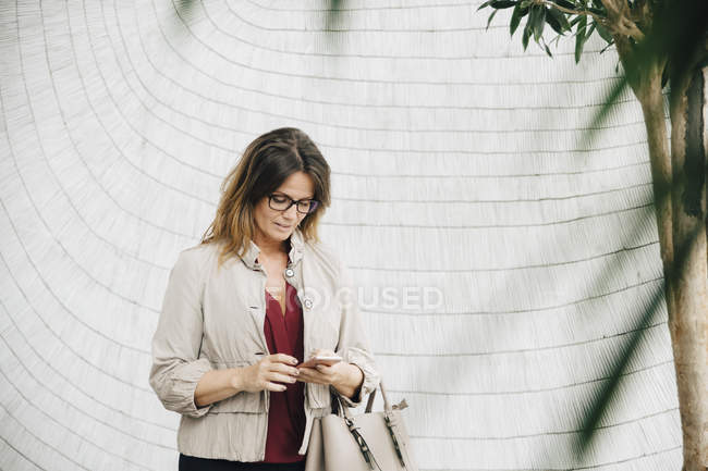 Businesswoman using smart phone while standing against wall at office — Stock Photo