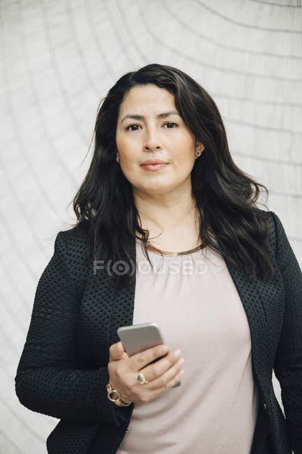 Ritratto di donna d'affari fiduciosa che tiene lo smartphone in piedi contro il muro in ufficio — Foto stock