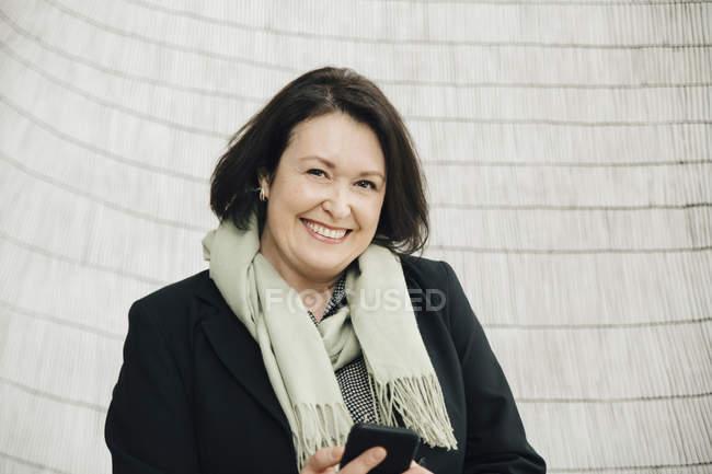 Retrato de mulher de negócios madura sorridente segurando telefone inteligente de pé contra a parede no escritório — Fotografia de Stock