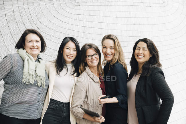 Portrait of smiling multi-ethnic businesswomen standing against wall at workplace — Stock Photo