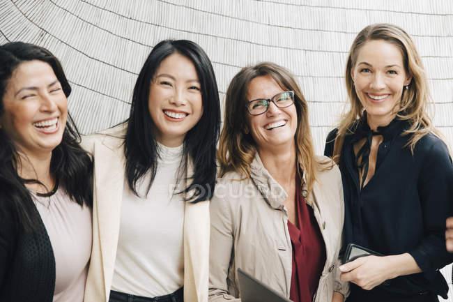 Ritratto di felici imprenditrici multietniche in piedi contro il muro — Foto stock