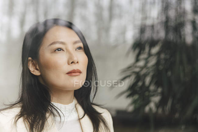 Thoughtful mid adult businesswoman looking through window at office — Stock Photo