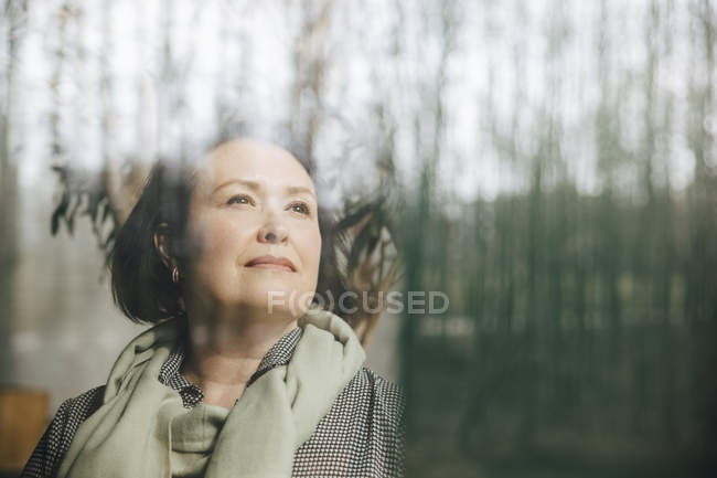 Thoughtful businesswoman looking through window at workplace — Stock Photo