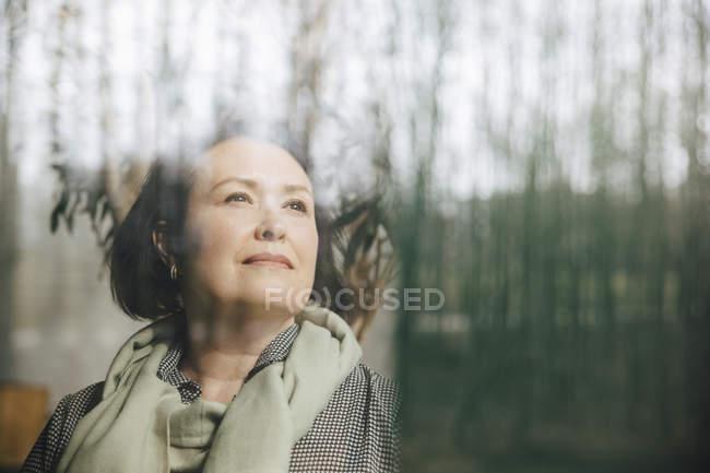 Imprenditrice premurosa che guarda attraverso la finestra sul posto di lavoro — Foto stock