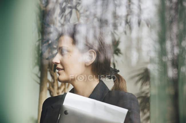 Donna d'affari fiduciosa distogliendo visto attraverso la finestra in ufficio — Foto stock