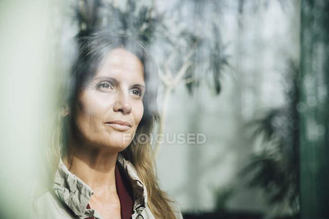 Задумчивая зрелая деловая женщина смотрит в окно офиса — стоковое фото