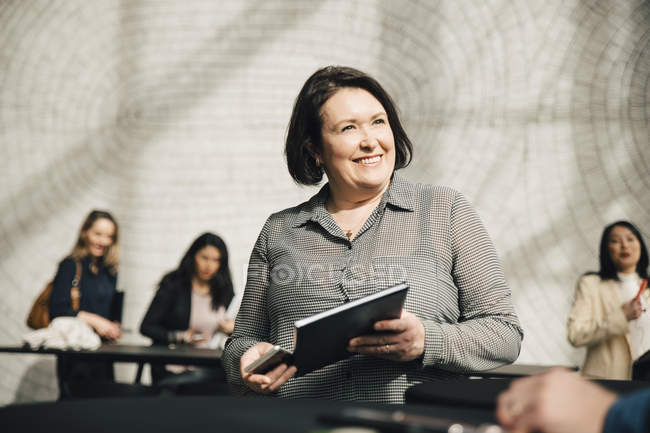 Smiling businesswoman looking at businessman during meeting in office — Stock Photo