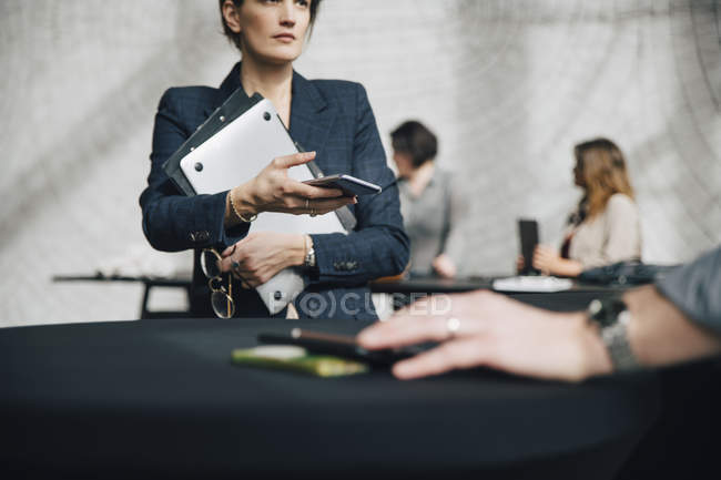 Midsection of businesswoman holding technologies while sitting at desk during meeting in office — Stock Photo