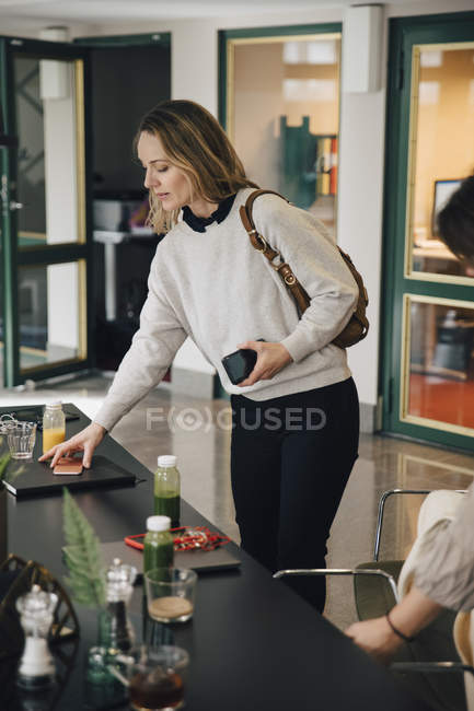 Confident businesswoman standing with female colleague at conference table in office during meeting — Stock Photo
