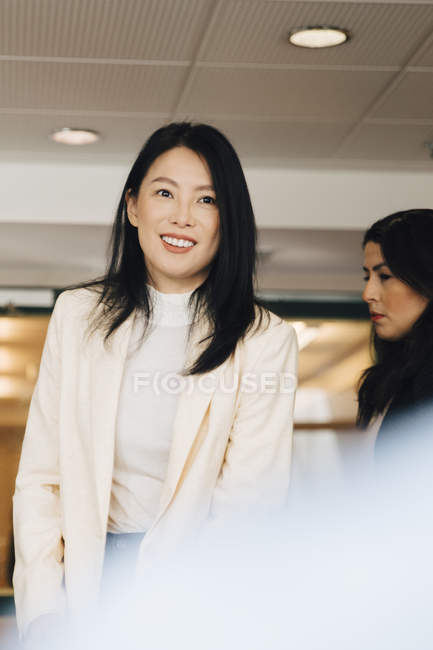 Smiling businesswoman standing amidst female colleagues during meeting in event — Stock Photo