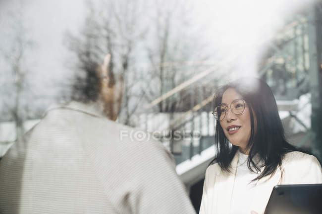 Smiling businesswoman discussing with coworker in office — Stock Photo