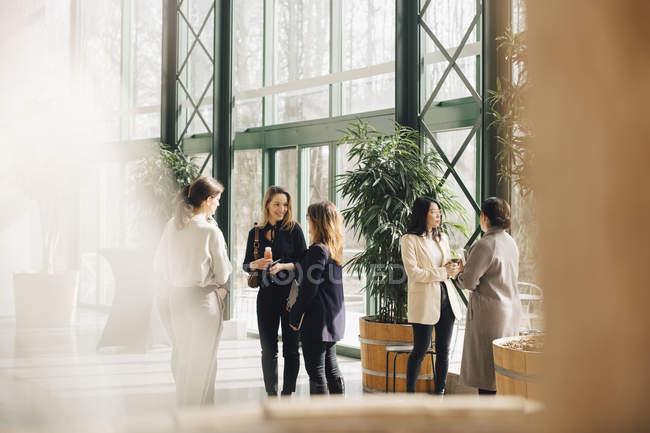 Улыбаясь многоэтнических женщин-профессионалов сетей в конференции событие — стоковое фото