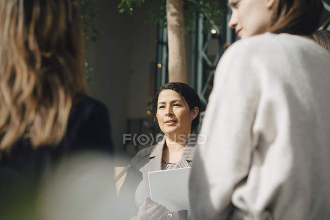 Confident businesswoman with colleagues in conference meeting — Stock Photo
