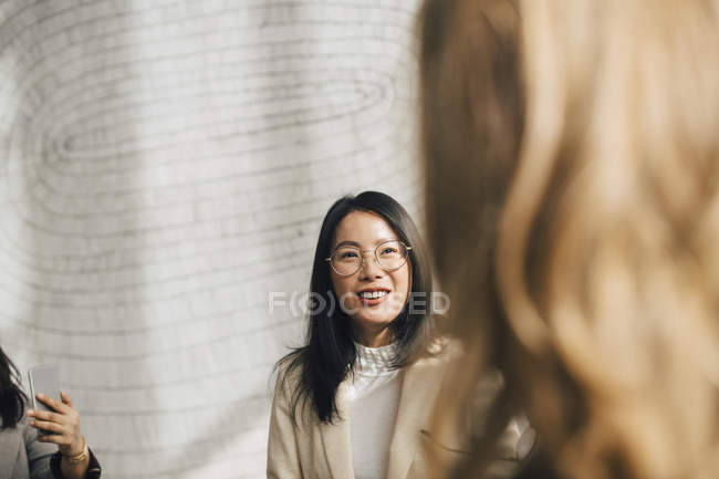 Smiling businesswoman listening to female coworker in meeting — Stock Photo