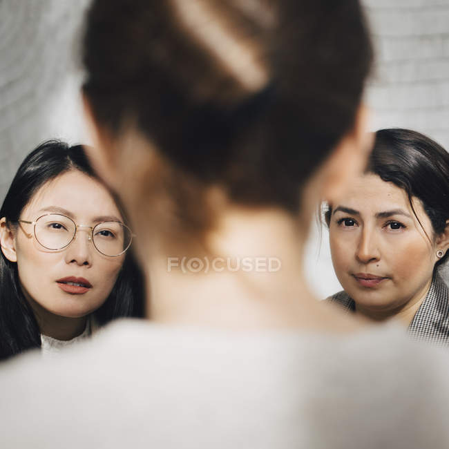 Female colleagues listening to businesswoman in meeting at office — Stock Photo