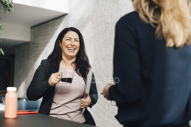 Smiling businesswoman having coffee while talking to colleague at conference — Stock Photo