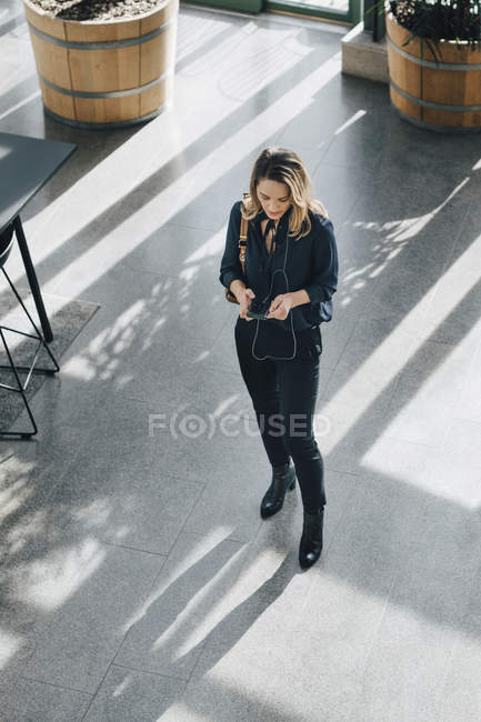 Longitud completa de la mujer de negocios usando el teléfono inteligente mientras está de pie en la oficina - foto de stock
