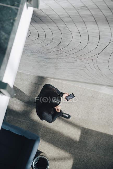 Comprimento total de empresária usando telefone inteligente enquanto caminha no corredor no escritório — Fotografia de Stock