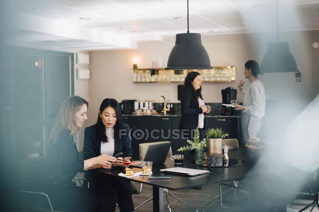 Donne d'affari che utilizzano smartphone al tavolo conferenze mentre i colleghi in piedi in background — Foto stock