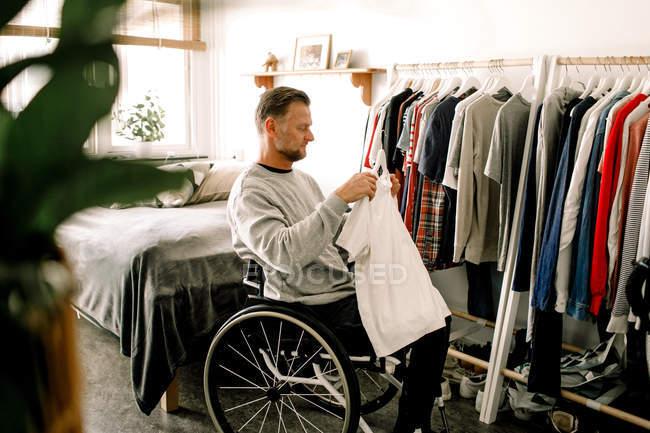 Вид сбоку пожилого мужчины-инвалида в белой футболке, сидящего дома на инвалидной коляске у вешалки для одежды — стоковое фото