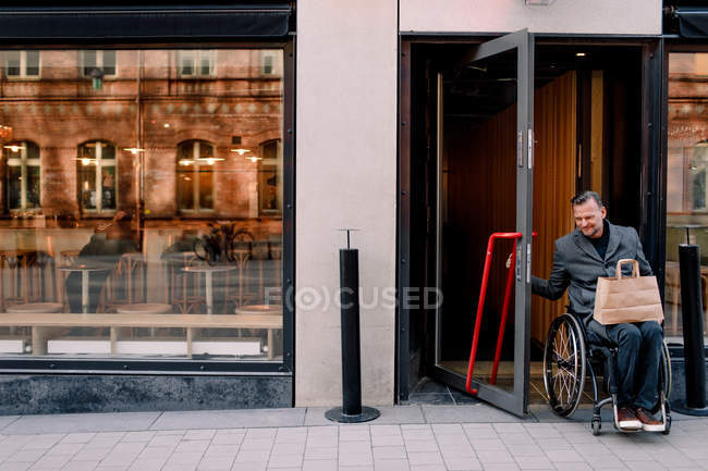 Disabled mature man with shopping bag leaving store in city — Stock Photo