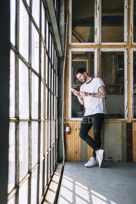 Lunghezza completa di fiducioso hipster hacker maschile utilizzando smart phone da finestra in ufficio creativo — Foto stock