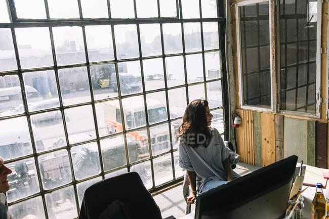 Mujer joven empresaria sentada en silla contra ventana en la sala de juntas en un lugar de trabajo creativo - foto de stock