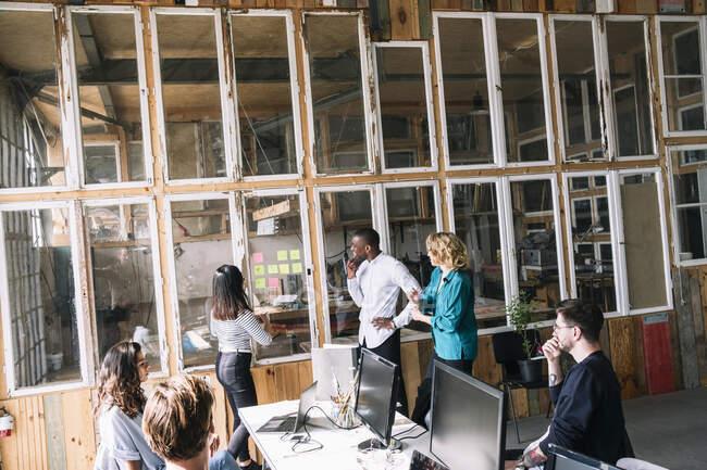 Equipo de hackers informáticos discutiendo sobre notas adhesivas en la pared de cristal en la sala de bordo durante la reunión en la oficina creativa. - foto de stock