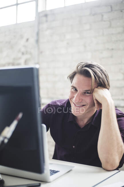 Portrait of smiling young male programmer coding at desk in office — Stock Photo