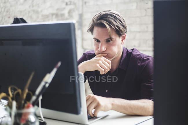 Besorgter professioneller Hacker schaut in Kreativbüro auf Laptop — Stockfoto