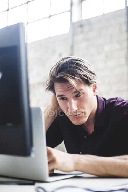 Young male entrepreneur working on start-up project while coding at desk in office — Stock Photo