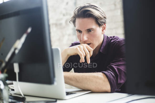 Serious male IT professional thinking while coding in laptop at creative workplace — Stock Photo