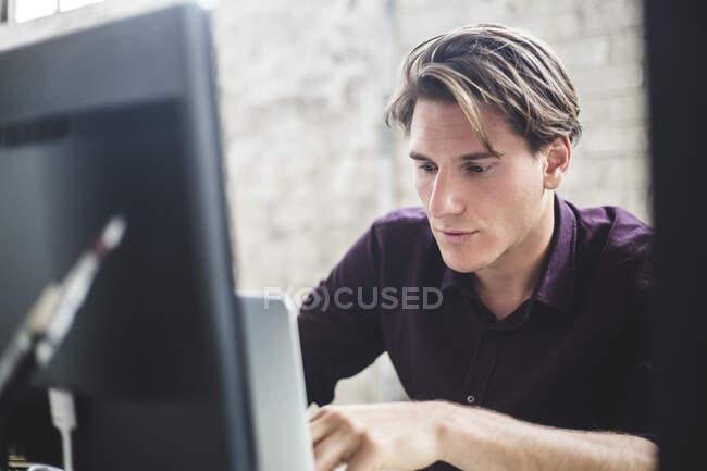 Männliche Computerprogrammierer mit Laptop während der Arbeit im Büro — Stockfoto