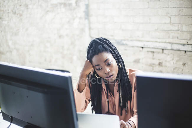 High angle view of young female computer hacker coding at desk in office — Stock Photo