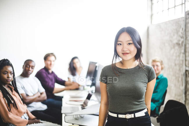 Portrait of smiling female IT expert with coworkers in background at workplace — Stock Photo