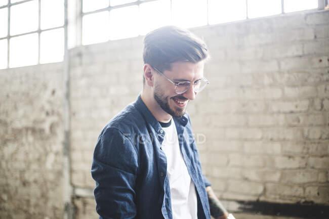 Sorridente barbuto uomo d'affari indossando smart casual mentre si lavora in azienda IT — Foto stock