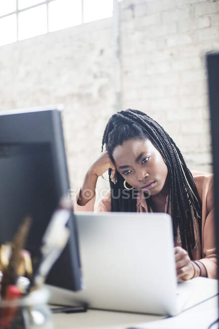 Nachdenkliche Programmiererin schaut im Büro auf Laptop — Stockfoto