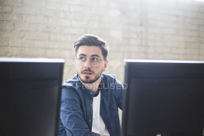 Young entrepreneur looking away while working on computer programs in creative office — Stock Photo