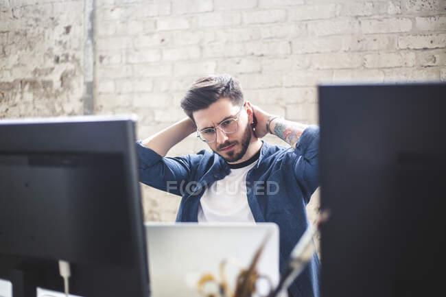Ernsthafter junger Computerprogrammierer schaut im Büro auf Laptop — Stockfoto